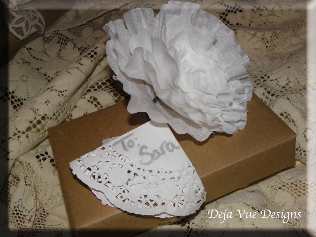gift wrapped in brown paper and accented with paper flower and lace