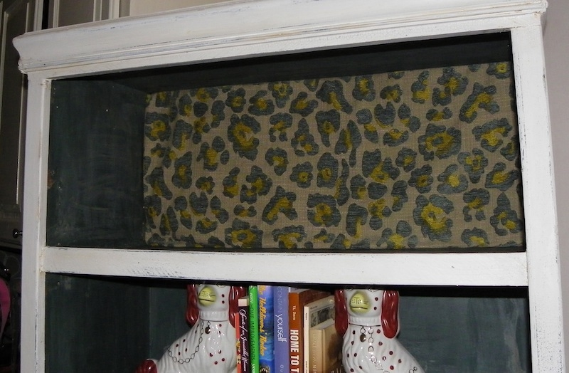 Lining a bookcase with leopard print wallpaper